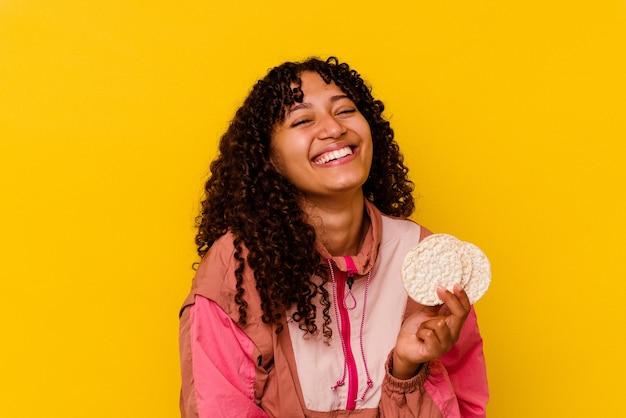 Jeune femme de sport de race mixte tenant une galette de riz isolée sur fond jaune en riant et en s'amusant.