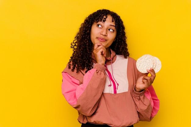 Jeune femme de sport de race mixte tenant des gâteaux de riz isolés sur du jaune regardant de côté avec une expression douteuse et sceptique.