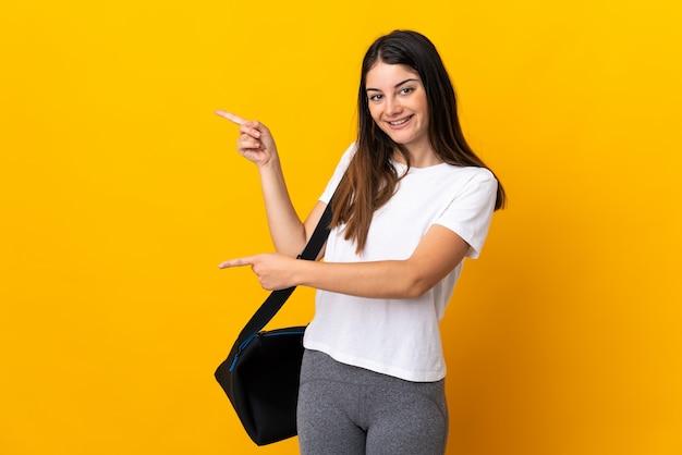 Jeune femme de sport avec sac de sport isolé sur le doigt pointé jaune sur le côté et présentant un produit