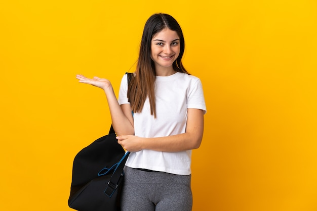 Jeune femme de sport avec sac de sport isolé sur fond jaune holding copyspace imaginaire sur la paume pour insérer une annonce