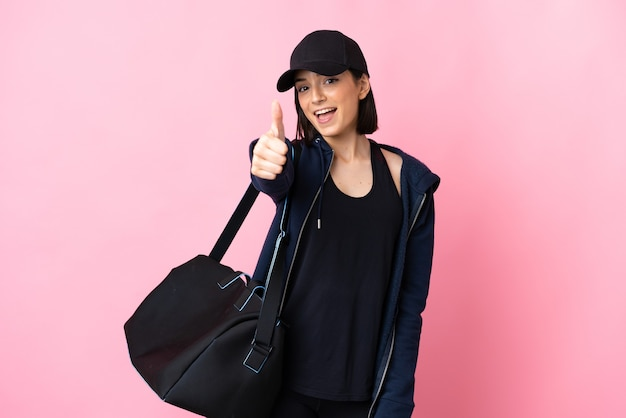 Jeune femme de sport avec sac de sport isolé sur fond rose avec les pouces vers le haut parce que quelque chose de bien s'est passé