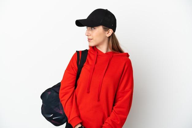 Jeune femme de sport avec sac de sport isolé sur un mur blanc à la recherche sur le côté