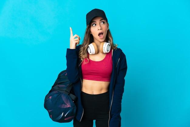 Jeune femme de sport avec sac de sport isolé sur mur bleu dans l'intention de réaliser la solution tout en soulevant un doigt