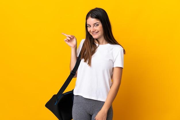 Jeune femme de sport avec sac de sport isolé sur mur jaune doigt pointé sur le côté
