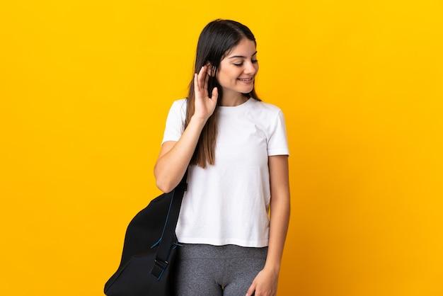 Jeune femme de sport avec sac de sport isolé sur mur jaune en écoutant quelque chose en mettant la main sur l'oreille