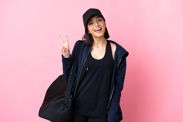 Jeune femme de sport avec sac de sport isolé sur mur rose souriant et montrant le signe de la victoire