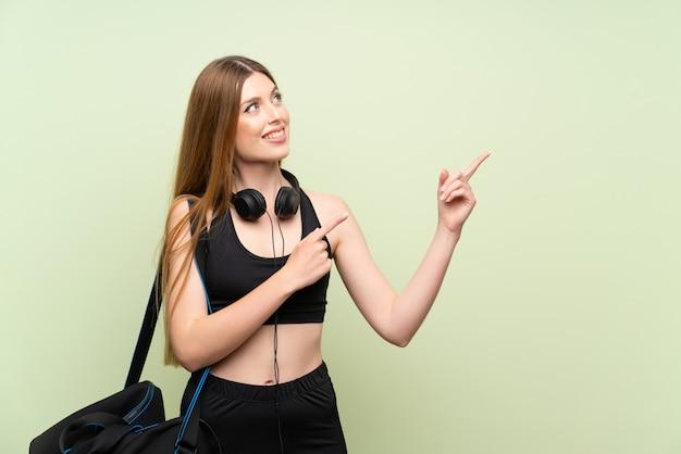 Jeune femme de sport sur vert isolé pointant avec l'index une excellente idée