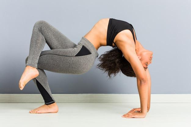 Jeune femme sportive afro-américaine faisant des poses de gymnastique rythmique