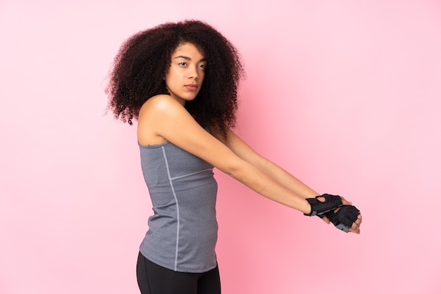 Jeune femme sportive afro-américaine isolée sur l'étirement rose