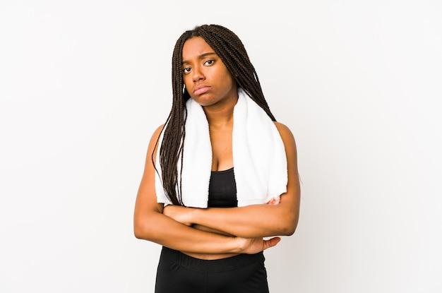Jeune femme sportive afro-américaine isolée malheureuse à la recherche à huis clos avec une expression sarcastique.