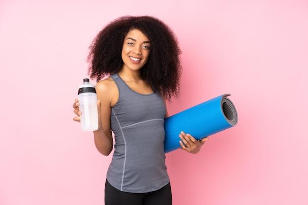 Jeune femme sportive afro-américaine isolée sur rose avec bouteille d'eau de sport et avec un tapis