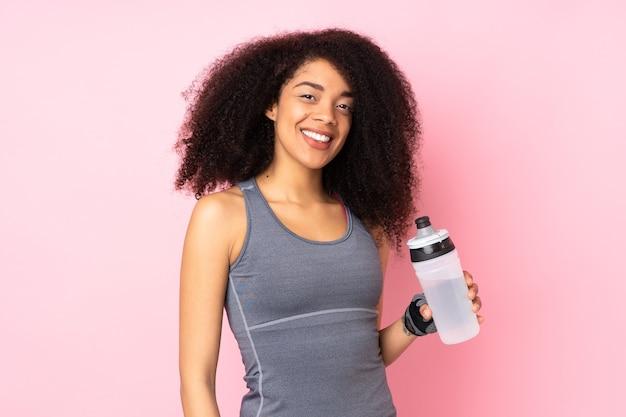 Jeune femme sportive afro-américaine isolée sur rose avec bouteille d'eau de sport