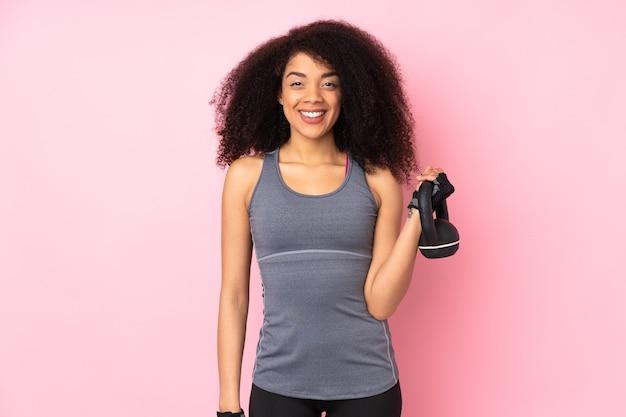 Jeune femme sportive afro-américaine isolée sur rose faisant de l'haltérophilie avec kettlebell