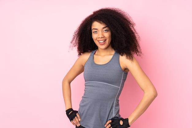 Jeune femme sportive afro-américaine isolée sur rose heureux et souriant