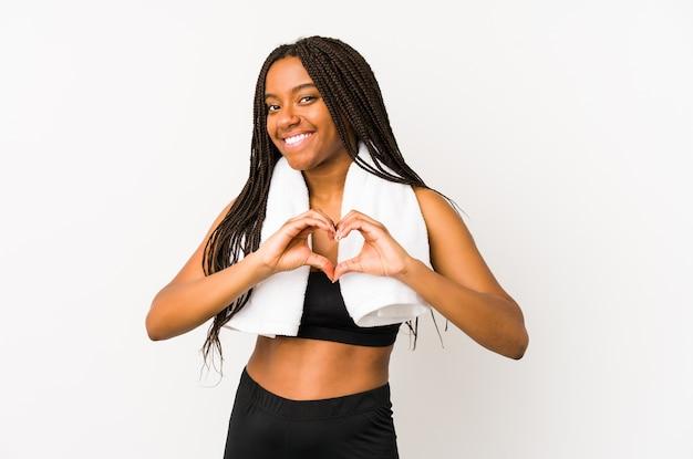 Jeune femme sportive afro-américaine isolée souriant et montrant une forme de coeur avec les mains.