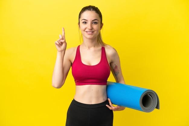 Jeune femme sportive allant à des cours de yoga tout en tenant un tapis pointant vers une excellente idée
