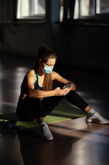 Jeune femme sportive après avoir pratiqué le yoga, pause en faisant de l'exercice, se détendre sur un tapis de yoga