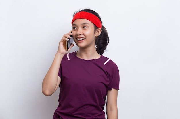 Jeune femme sportive asiatique utilisant un téléphone portable sur fond blanc