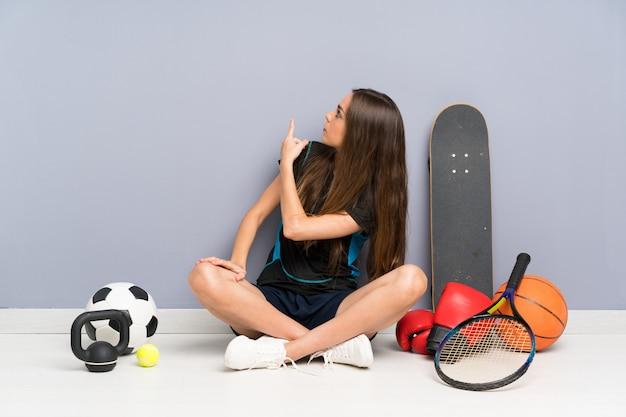 Jeune femme sportive assise sur le sol en arrière avec l'index