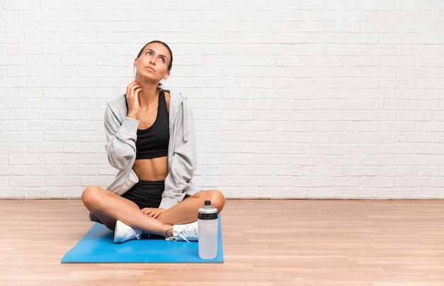 Jeune femme sportive assise sur le sol avec un tapis pensant une idée