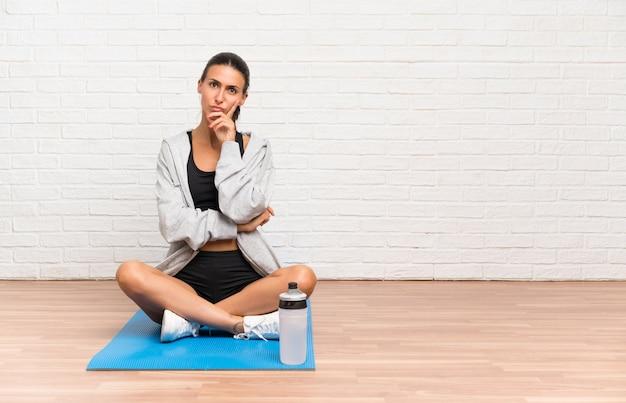 Jeune femme sportive assise sur le sol avec un tapis, pensant à une idée