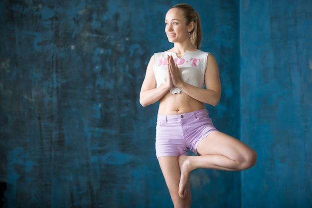 Une jeune femme sportive attrayante faisant une pose de vrksasana