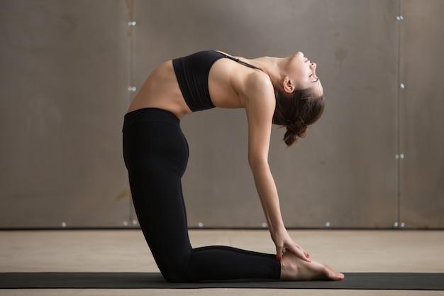 Jeune femme sportive attrayante en posture de chameau, studio gris backgro