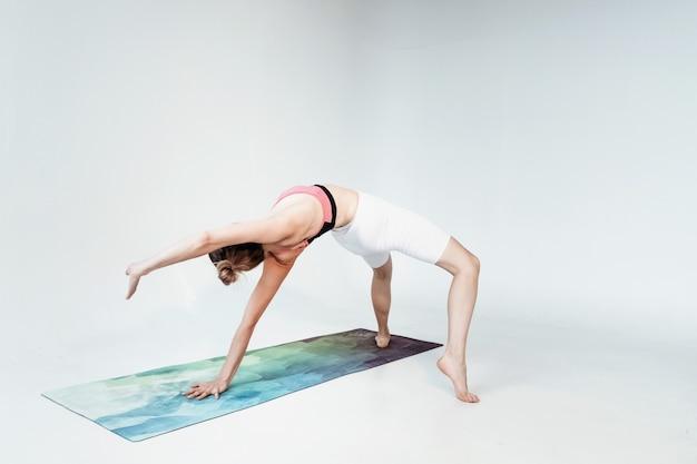 Jeune femme sportive attrayante souriante pratiquant le yoga, méditant dans la pose de demi-lotus avec namaste.