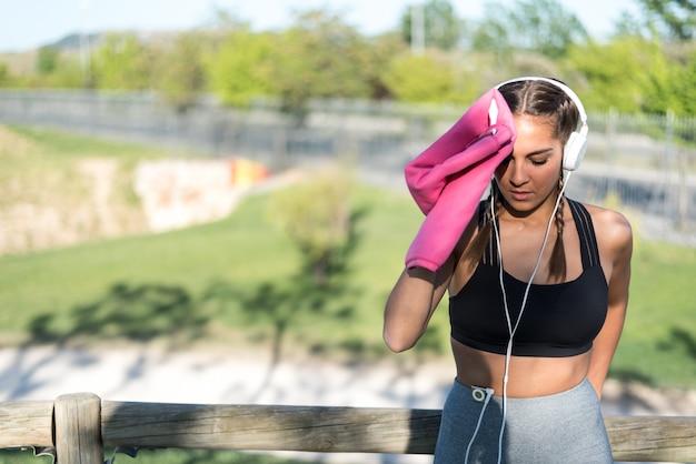 Jeune femme sportive au repos et essuyant sa sueur avec une serviette.