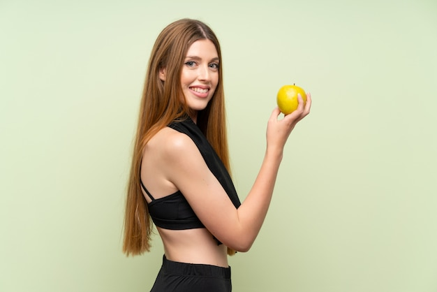 Jeune femme sportive au vert isolé avec une pomme