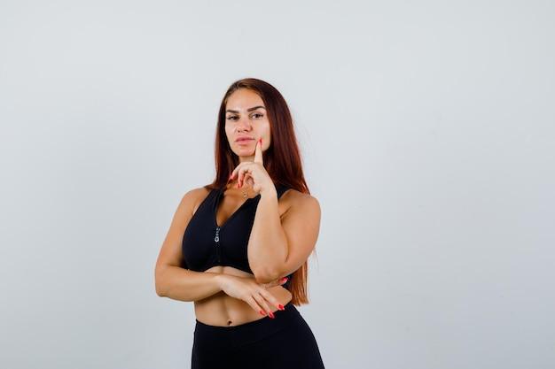 Jeune femme sportive aux cheveux longs dans un haut noir