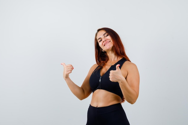 Jeune femme sportive aux cheveux longs montrant les pouces vers le haut
