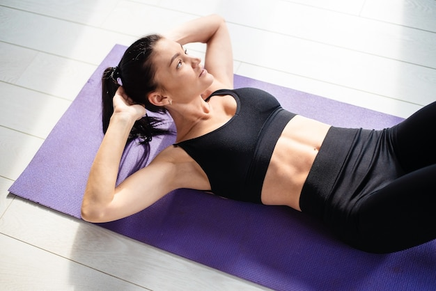 Jeune femme sportive aux cheveux noirs allongée sur un tapis de yoga et faisant des exercices d'abs. charmante femme en vêtements de sport profitant d'une séance d'entraînement matinale à la maison.