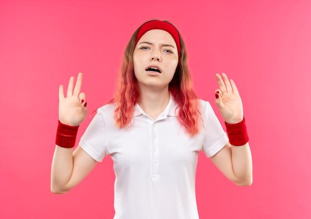 Jeune femme sportive en bandeau relaxant faisant le geste de méditation avec les doigts debout sur le mur rose
