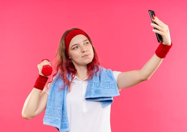 Jeune femme sportive en bandeau avec une serviette sur l'épaule en prenant un selfie d'elle-même montrant l'haltère à la main à la caméra de son smartphone debout sur le mur rose
