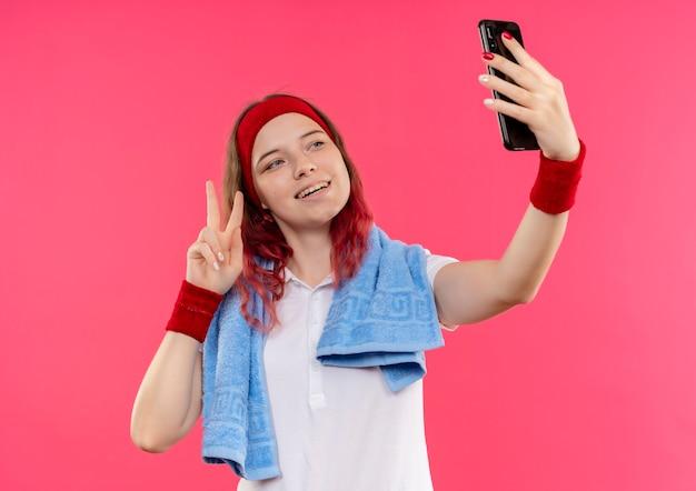 Jeune femme sportive en bandeau avec une serviette sur l'épaule en prenant un selfie d'elle-même montrant le signe de la victoire à la caméra de son smartphone debout sur un mur rose