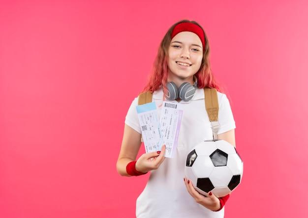 Jeune femme sportive en bandeau tenant deux billets d'avion et ballon de football souriant joyeusement debout sur le mur rose