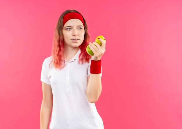 Jeune femme sportive en bandeau tenant deux pommes à côté positif et heureux debout sur le mur rose