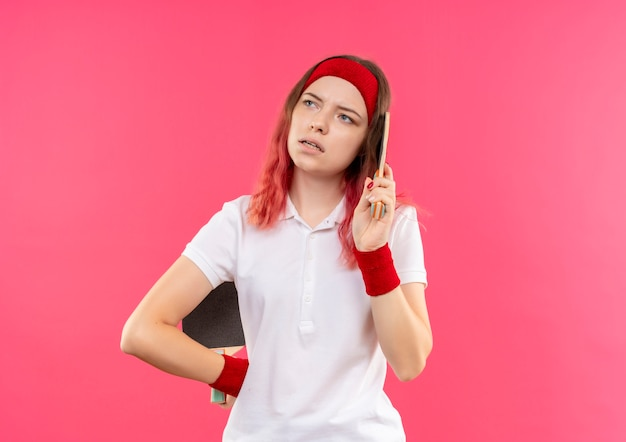 Jeune femme sportive en bandeau tenant deux raquettes pour le tennis de table à côté avec une expression pensive sur le visage debout sur un mur rose