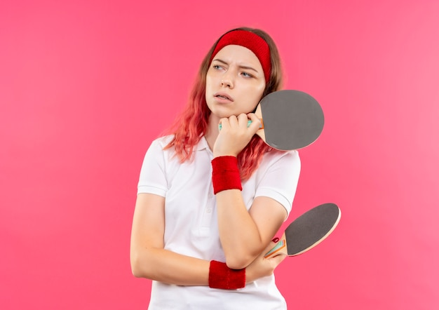 Jeune femme sportive en bandeau tenant une raquette pour le tennis de table à côté avec une expression pensive sur le visage pensant debout sur un mur rose