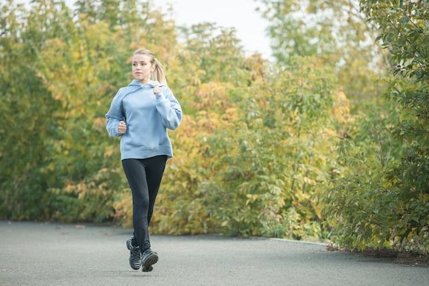 Jeune femme sportive blonde en vêtements de sport jogging sur route dans un parc contre des arbres verts et jaunes le matin en automne