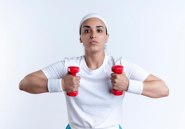 Jeune femme sportive caucasienne confiante portant des exercices de bandeau et de bracelets avec des haltères isolés sur un espace blanc avec copie espace
