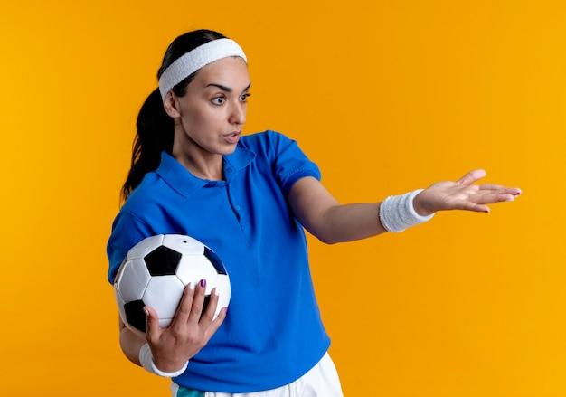 Jeune femme sportive caucasienne confuse portant bandeau et bracelets tient la balle pointant sur le côté isolé sur fond orange avec copie espace