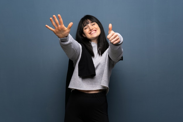 Jeune femme sportive comptant six avec les doigts