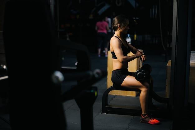 Jeune femme sportive avec un corps athlétique parfait portant des vêtements de sport noirs à la recherche d'un bracelet de remise en forme tout en étant assise sur un simulateur et se prépare à s'entraîner dans une salle de sport sombre. concept de mode de vie sain.