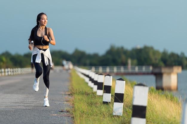 Jeune femme sportive courant sur la route dans la belle nature