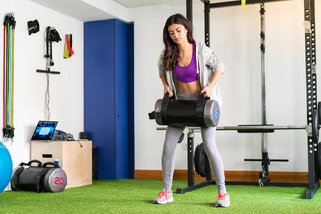 Jeune femme sportive dans une salle de sport faisant de l'haltérophilie