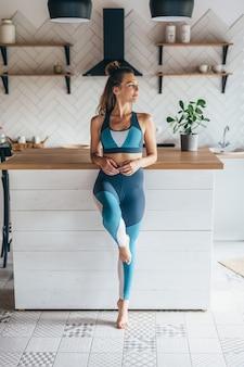 Jeune femme sportive debout dans la cuisine.