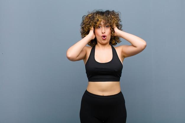 Jeune femme sportive à la désagréablement choqué, effrayé ou inquiet, la bouche grande ouverte et couvrant les deux oreilles avec les mains contre le mur gris