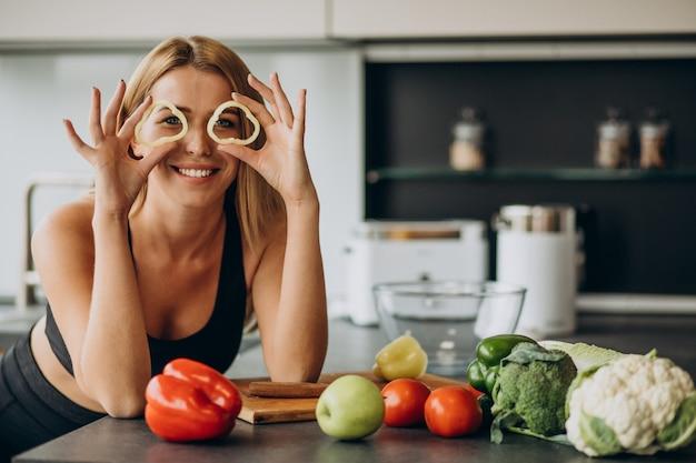 Jeune femme sportive avec du poivre dans la cuisine